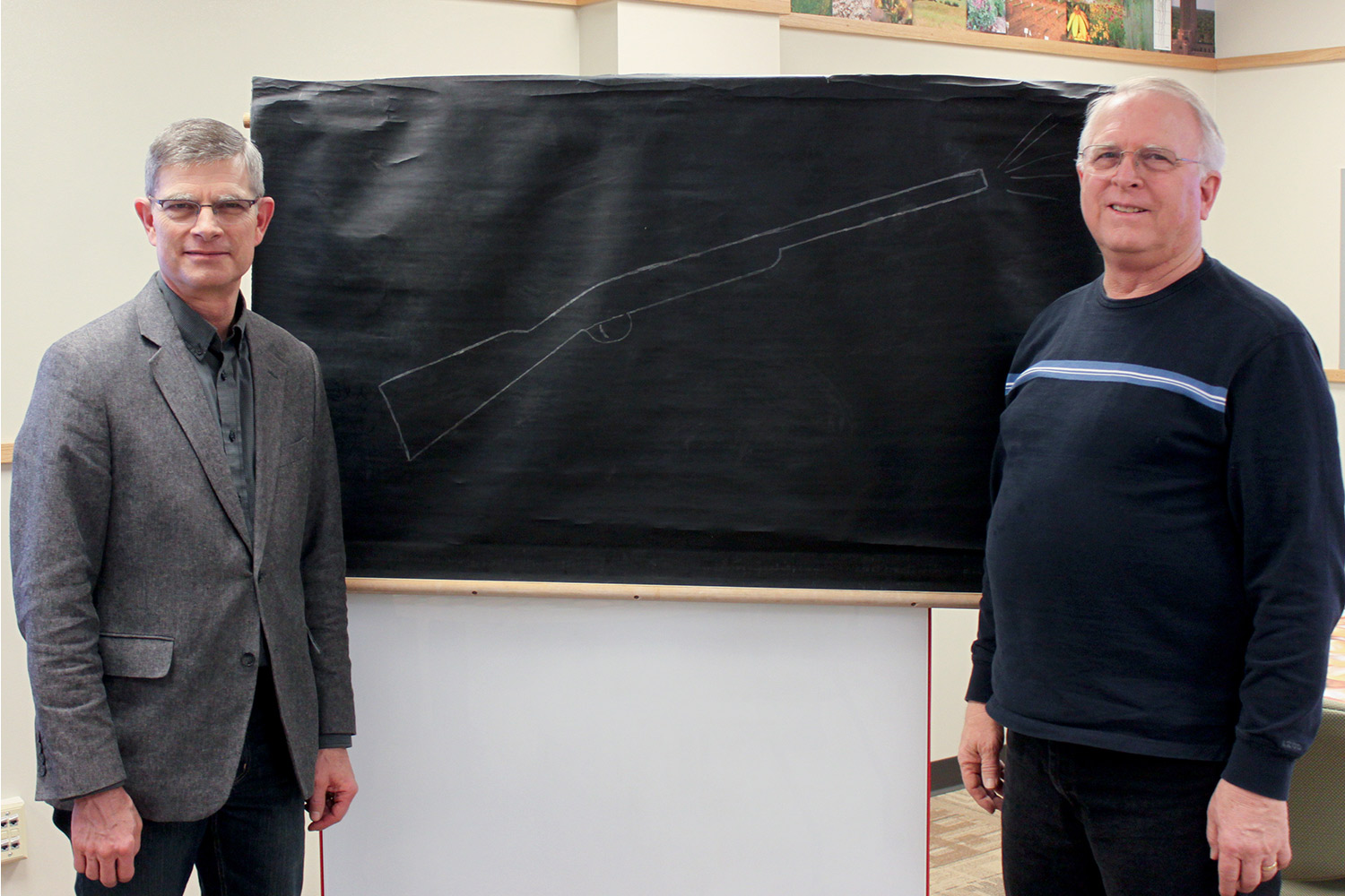 Thomas and Birdie Goodding's grandsons, Gary Goodding (left) and Rich Goodding (right), pose in the newly remodeled Goodding Learning Center with the drawing Dr. Goodding used to announce class quizzes.