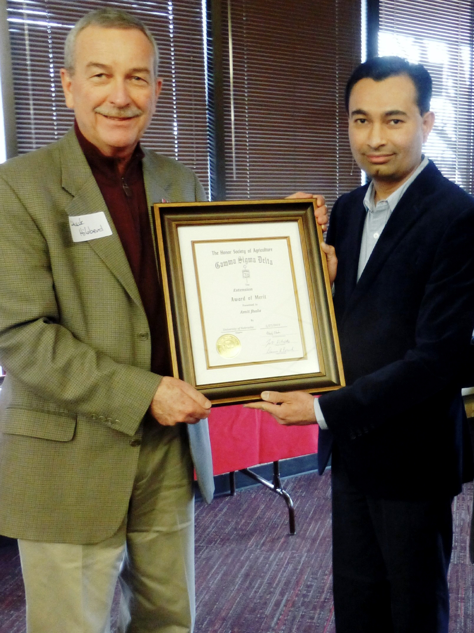 Chuck Hibberd presenting The Honor Society of Agriculture Gamma Sigma Delta Extension Award of Merit to Amit Jhala.