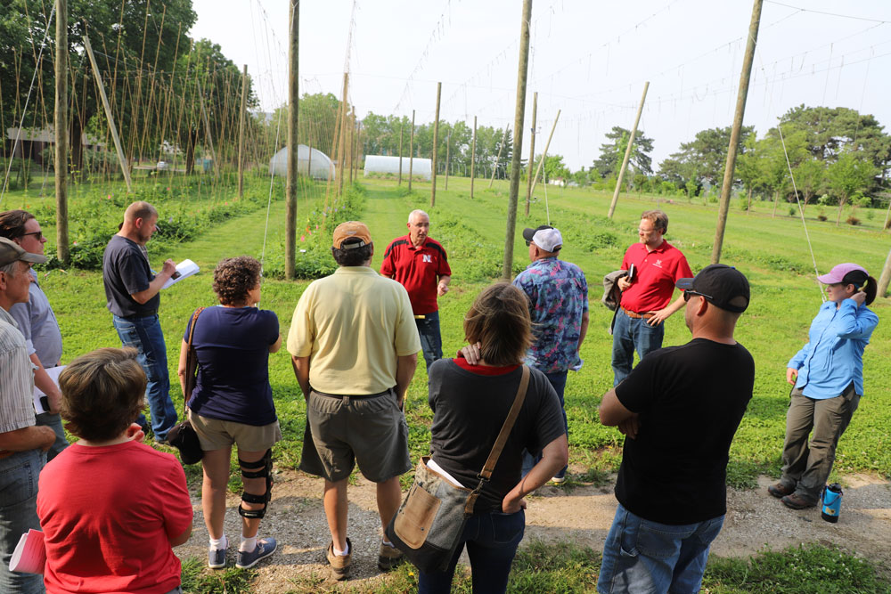 Stacy Adams, Keenan Amundsen and Allison Butterfield speak to hop workshop participants at the University of Nebraska–Lincoln East Campus hop yard May 31.