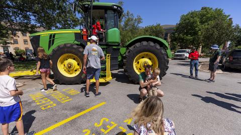 Children examine a John Deere tractor during East Campus Discovery Days on June 12. Craig Chandler | University Communication
