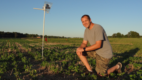 Greg Kruger, weed science extension specialist at the University of Nebraska-Lincoln, kneels in a soybean field that recently received a treatment of dicamba. He continues to conduct research on dicamba drift and boom heights.