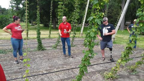 Milos Zaric, a Nebraska doctoral student in agronomy and horticulture (center), presents the 3/4-acre hop yard associated with his work at the West Central Research, Extension and Education Center in North Platte Aug. 21.