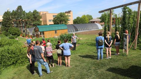 Nebraska high school students and their families listen to Stacy Adams, The Biggest Grower program coordinator, speak about speciality crop production near the East Campus Hops Planting Garden on June 30.