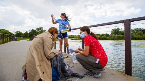 Malayna Wingert, a sophomore biological systems engineering major from Sterling, Nebraska, lifts a water sample out of Holmes Lake as Anni Poetz and Maddie Carpenter record data in August 2020. The students worked under faculty member Jess Corman this summer through Nebraska's UCARE program.