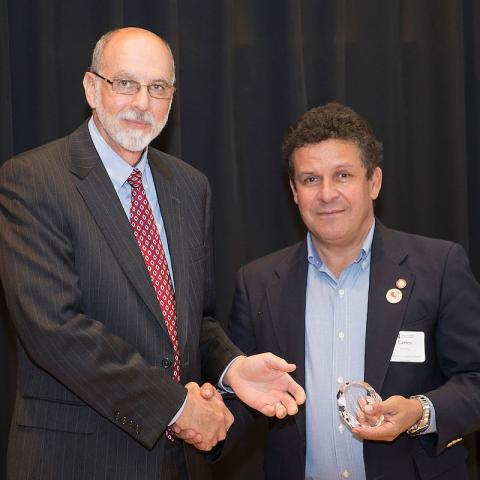 Ron Yoder presents an Omtvedt Innovation Award to Carlos Urrea